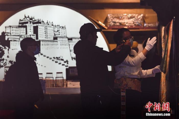 图为布达拉宫管理处做事人员为网友直播介绍馆藏的文物龙袍。中新社记者 何蓬磊 摄