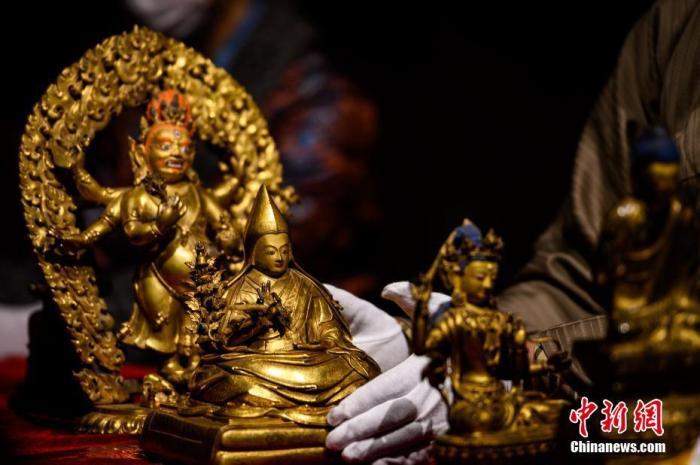 图为布达拉宫管理处做事人员为网友直播介绍馆藏的佛教造像文物。中新社记者 何蓬磊 摄