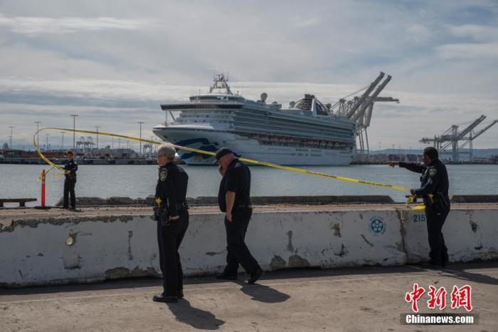 """当地时间3月9日,警方在""""至尊公主号""""邮轮停靠的奥克兰港拉起警戒线。在旧金山附近海域""""徘徊""""数天之后,""""至尊公主号""""邮轮于9日中午11时左右穿过金门大桥,不久后停靠在旧金山湾区的奥克兰港。乘客将陆续在这里下船,被送往指定地点接受治疗或隔离。中新社记者 刘关关 摄"""
