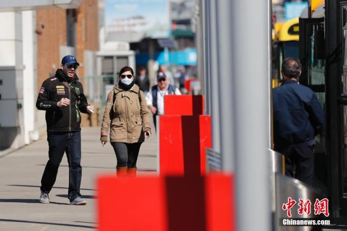 资料图:当地时间3月9日,一位民众戴口罩在纽约曼哈顿换乘公交。中新社记者 廖攀 摄