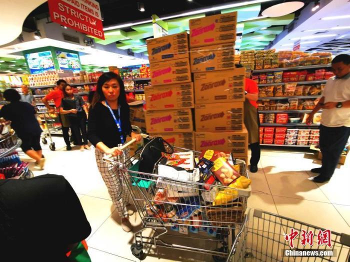 3月10日,位于马尼拉CBD马卡蒂的LANDMARK生活超市,不少家庭成车购买食物和生活用品,商场工作人员则不停补货。因应新冠肺炎疫情在菲出现本地传播迹象,菲律宾总统杜特尔特9日宣布全菲进入公共卫生紧急状态。<a target='_blank' href='http://www.chinanews.com/'>中新社</a>记者 关向东 摄