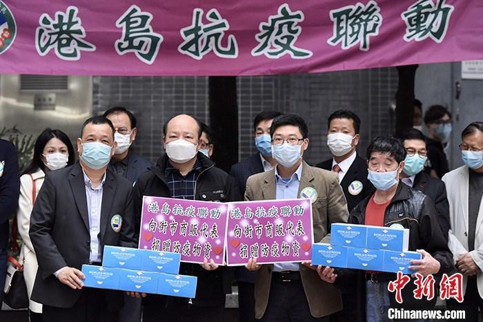 """3月11日下午,多位香港上环街市商贩出席活动领取口罩。由港岛各界社会团体及人士成立的""""港岛抗疫联动""""启动为期一周的香港岛社区商户探访,期间将派发35万个口罩给区内商户及街坊。<a target='_blank' href='http://www.chinanews.com/'>中新社</a>记者 李志华 摄"""