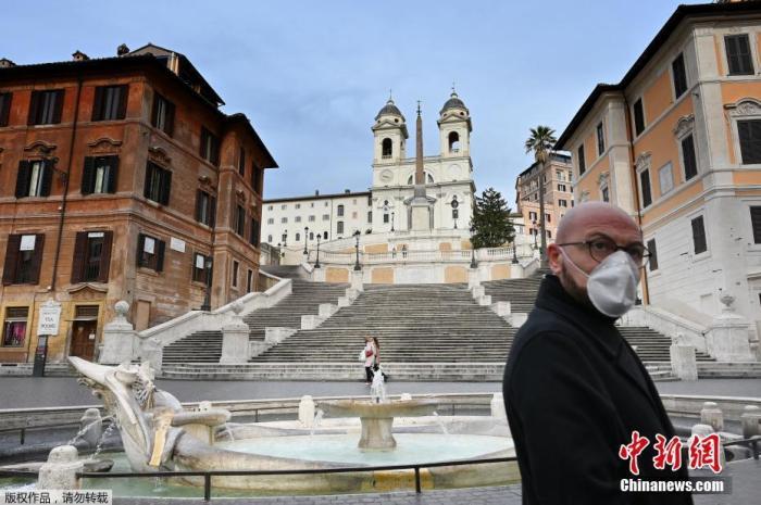 当地时间3月12日,意大利罗马市中心斯帕尼亚广场,一名戴着防护面具的男子走过台阶。