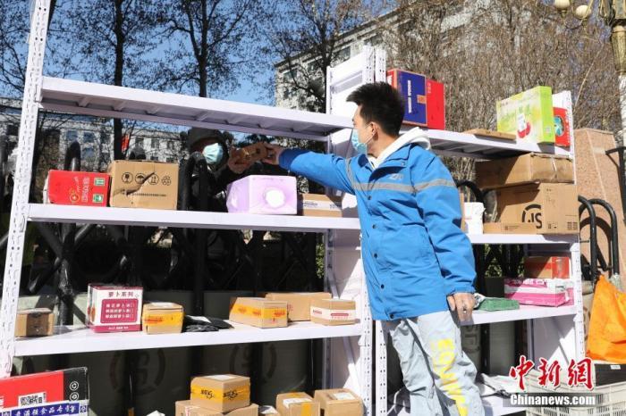"""3月12日,北京,快递小哥李杰通过围栏把包裹交给客户。李杰是中通快递北京厂洼路网点的一名快递员。他在9日作为快递小哥代表出席了国务院联防联控机制举行的新闻发布会,因此成为一名""""网红""""快递员。他每天早上七点开始一天的工作,一天之内要两次往返于快递网点和各个配送点之间。他为人热情,基本上所有的客户都认识他。正如他在发布会上所说的一样:""""我们就是想尽我们自己的力把快递送好,把客户服务好,在疫情期间把快件快速、安全的送到客户手中。我们最初的想法是让我们多走动,客户少出门。""""/p中新社记者 蒋启明 摄"""