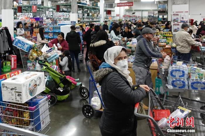当地时间3月13日,位于美国纽约皇后区的一家大型超市,民众排队购买物资。/p中新社记者 廖攀 摄
