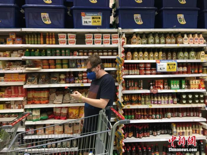 在巴西圣保罗,一名戴口罩的顾客在一家超市购物。中新社记者 莫成雄 摄