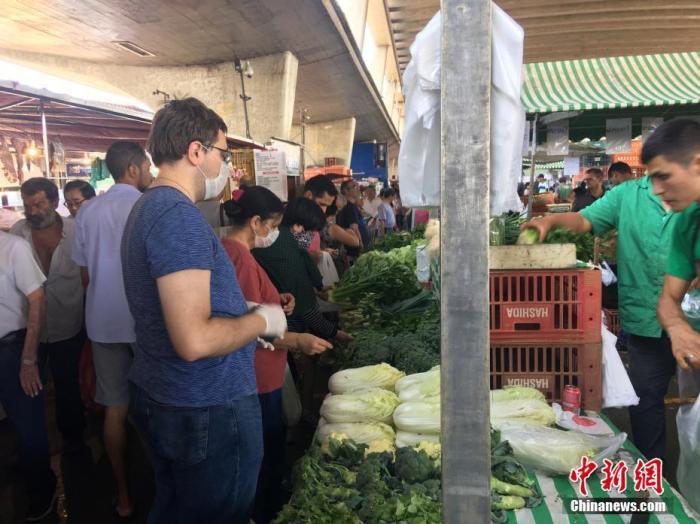 当地时间3月14日,在巴西圣保罗,几位戴口罩的民众在一家农贸市场选购蔬菜。随着新冠肺炎疫情的蔓延,现在圣保罗戴口罩的人越来越多。当地民众认为,面对新冠病毒来袭,佩戴口罩是最简单最有效的防护手段。中新社记者 莫成雄 摄