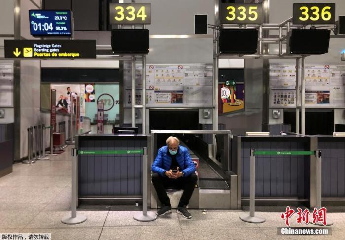 在西班牙马拉加的机场,一名男子戴着口罩等待他的航班起飞。