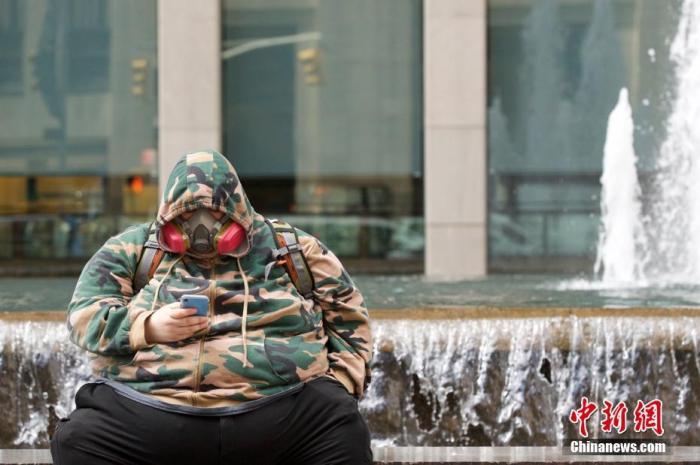 美国纽约市曼哈顿区街头,有人佩戴呼吸防护面具应对疫情。 中新社记者 廖攀 摄