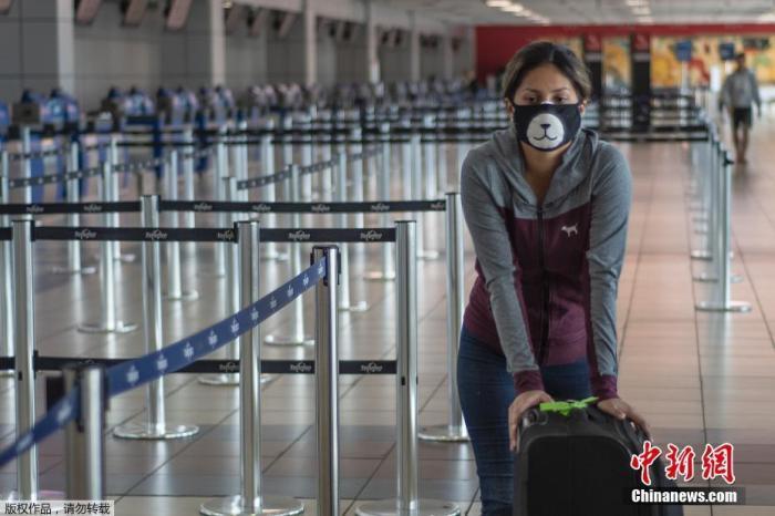 一名乘客戴着口罩走过巴拿马城托库曼国际机场。继欧洲航班暂停后,巴拿马政府又增加了对亚洲航班的禁令。