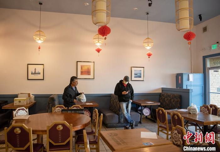 """当地时间3月16日,一名戴口罩的顾客在美国旧金山湾区米尔布雷一家湖南菜馆等餐。这家菜馆从当日开始实行""""无接触取餐"""",顾客网上下单,到店自取食物,饭店也可提供送餐服务。美国旧金山湾区6个县宣布实施出行禁令,要求居民在接下来的三个星期内尽可能留在家中,并与他人保持一定距离。中新社记者 刘关关 摄"""