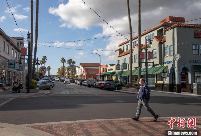 当地时间3月16日,一名戴口罩男子穿过美国旧金山湾区米尔布雷街头。美国旧金山湾区6个县当日宣布实施出行禁令,要求居民在接下来的三个星期内尽可能留在家中,并与他人保持一定距离。中新社记者 刘关关 摄
