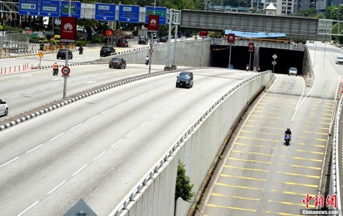 """当地时间3月18日,马来西亚政府正式开始实施""""行动限制令"""",关闭大部分政府机构、私营企业和商场及宗教场所。要求民众尽量留在家中。外卖顿时成为不少马来西亚民众选择,图为首都吉隆坡街头车辆稀疏。 陈悦 摄"""