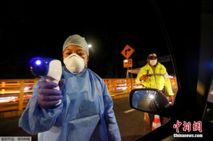 当地时间3月16日,哥伦比亚和厄瓜多尔之间的鲁米恰卡国际大桥上,一名厄瓜多尔卫生官员对车上的乘客进行体温测试。