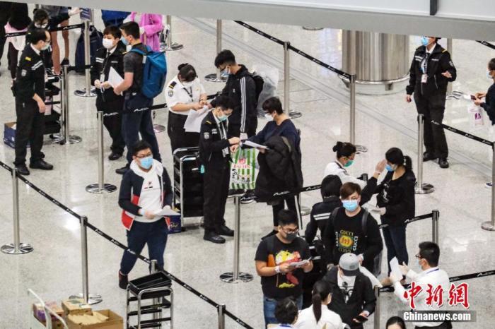 资料图为香港特区政府人员在机场禁区,为从各地到港人士戴上手带作强制检疫监察之用。/p中新社记者 秦楼月 摄