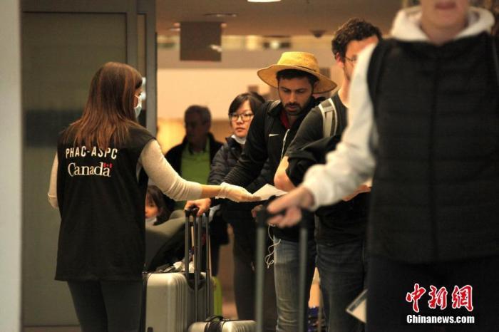 当地时间3月18日,加拿大多伦多皮尔逊国际机场,加拿大公共卫生署工作人员向抵港旅客派发防范新冠肺炎的宣传单。为防控新冠肺炎疫情,加拿大对非加国公民或永久居民的入境禁令从当日起生效。当局同日宣布,加拿大与美国之间的边境也将有限度关闭,出于休闲和旅游目的的跨境将不被允许。<a target='_blank' href='http://www.chinanews.com/'>中新社</a>记者 余瑞冬 摄