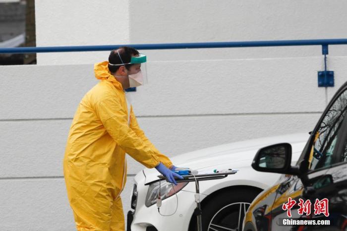 当地时间3月18日,美国纽约州拿骚县的一处医疗中心户外停车场,医务人员穿行其中为车辆中的民众提供新冠病毒检测。记者 廖攀 摄
