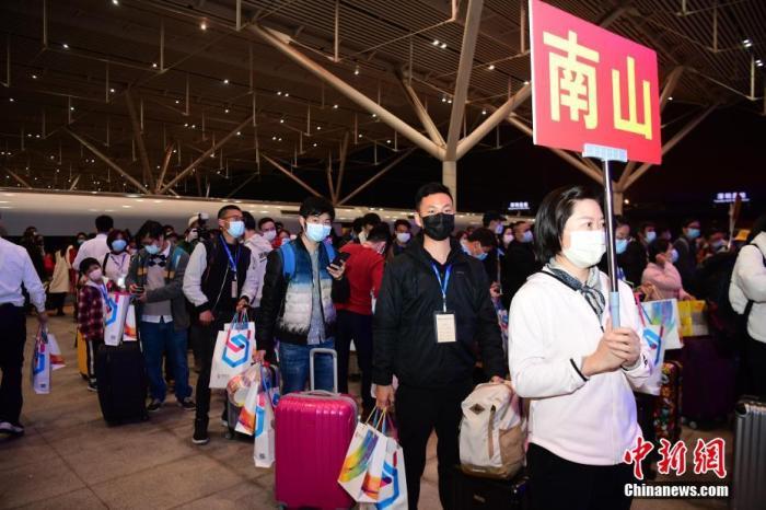 """资料图:3月19日晚,首趟""""点对点、一站式""""集中精准输送湖北务工人员G4315次专列抵达深圳北站,该趟专列从荆州发车,共有169人。当晚,深圳市人力资源和社会保障局组织相关部门工作人员前来接站。<a target='_blank' href='http://www.chinanews.com/'>中新社</a>记者 陈文 摄"""