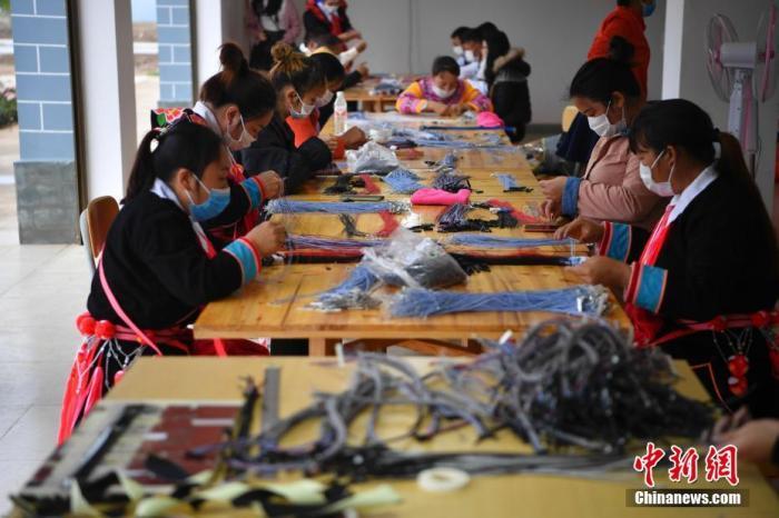 """资料图:工人在扶贫车间工作,实现""""家门口就业""""。 中新社记者 刘冉阳 摄"""