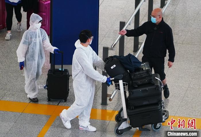 3月20日,从英国伦敦飞香港的航班抵达香港国际机场,所有旅客手腕上都戴上了电子监察手带,同时携带家居检疫指引资料。图为做足防护措施的旅客抵达机场。中新社记者 张炜 摄