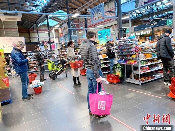 图为20日当天,柏林一家超市等待付款的人们相互隔开了1.5米的距离。<a target='_blank' href='http://www.chinanews.com/'>中新社</a>记者 彭大伟 摄