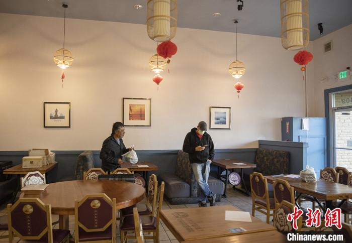 """当地时间3月16日,一名戴口罩的顾客在美国旧金山湾区米尔布雷一家餐馆等餐。这家菜馆从当日开始实行""""无接触取餐"""",顾客网上下单,到店自取食物,饭店也可提供送餐服务。旧金山湾区六县当地时间16日颁布禁令,要求居民翌日起在接下来的三周内尽可能留在家中。因为""""必要活动""""出门,需与他人保持6英尺""""社交距离""""。19日,加州州长在全州范围内颁布了一条类似的禁令。<a target='_blank' href='http://www.chinanews.com/'>中新社</a>记者 刘关关 摄"""