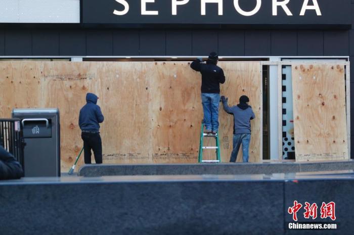 当地时间3月21日,美国纽约时代广场一个已经停业的商家,工作人员用木板封闭大门。<a target='_blank' href='http://www.chinanews.com/'>中新社</a>记者 廖攀 摄