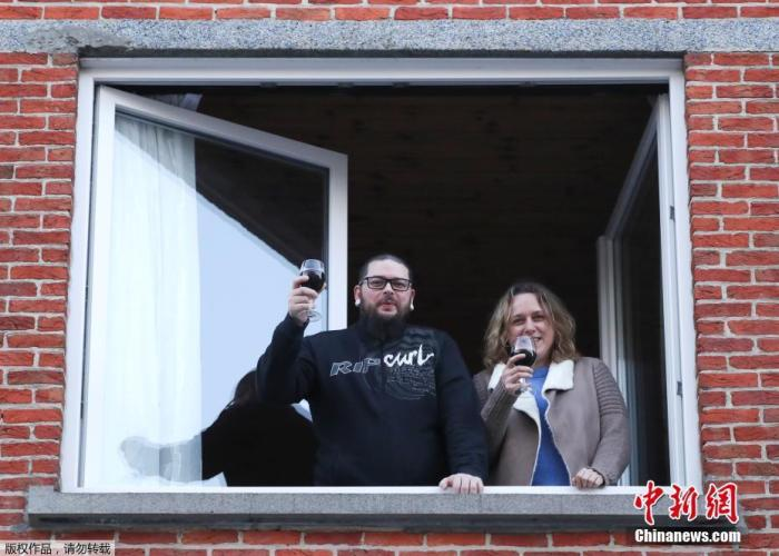 """内地时间3月22日,比利时首都布鲁塞尔安德莱赫特镇,在内地当局实施封闭期间,住民们在""""安详间隔""""的前提下颇有典礼感的举办餐前敬酒。"""