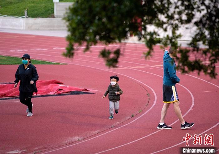 """当地时间3月22日,美国北加州圣马特奥县居民戴口罩在一处操场上散步。随着新冠肺炎疫情持续蔓延,加州的相关医疗资源愈发紧张。应州长加文·纽瑟姆的要求,美国总统特朗普当天宣布加州为新冠肺炎疫情""""重大灾区""""。<a target='_blank' href='http://www.chinanews.com/'>中新社</a>记者 刘关关 摄"""