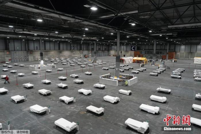 3月24日消息,近日西班牙马德里会展中心改造为方舱医院并开始接收患者。图为当地时间3月21日方舱医院内布置的床位。