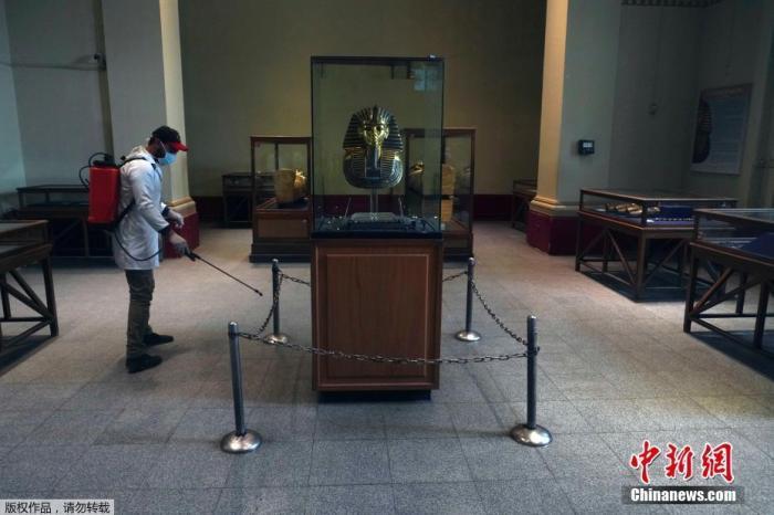 当地时间3月23日,一名男子在位于埃及首都开罗市中心的埃及博物馆内进行消毒。