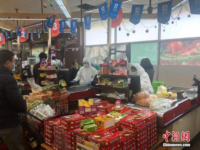 """纽约市华人聚居区法拉盛的一家华人超市内,收银员""""全副武装"""",穿戴防护服、口罩、手套工作。中新社记者 马德林 摄"""
