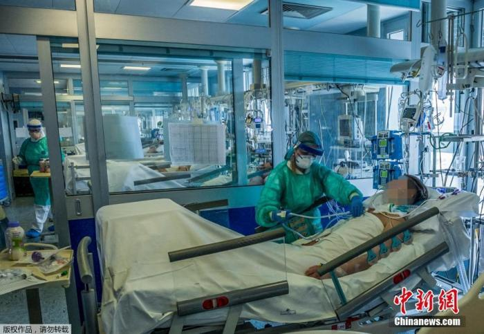 当地时间3月23日,意大利米兰东南部的克雷莫纳医院重症监护室里,医护人员正在为感染新冠状肺炎的重症患者治疗。