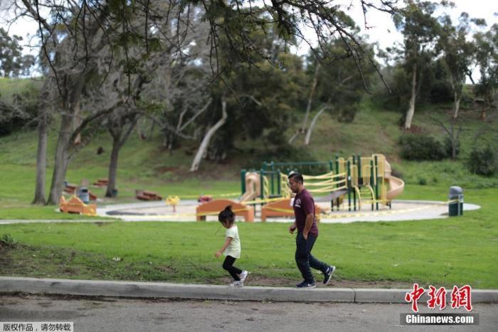 资料图:当地时间3月23日,在美国加利福尼亚州洛杉矶,一对父母走过一个封闭的游乐场。