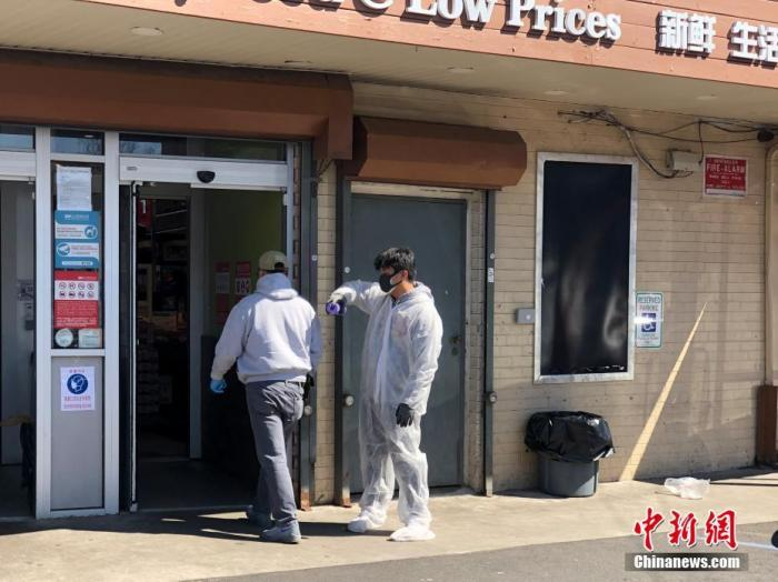 """截至当地时间3月24日上午,全美新冠病毒感染者超过4万,遍布50个州。纽约州感染者2万多,接近全国一半,被媒体称为美国疫情的""""震中""""。图为纽约市华人聚居区法拉盛的一家华人超市门前,一名身穿防护服的超市员工正在向进入超市的顾客喷洒消毒剂。 <a target='_blank' href='http://www.chinanews.com/'>中新社</a>记者 马德林 摄"""