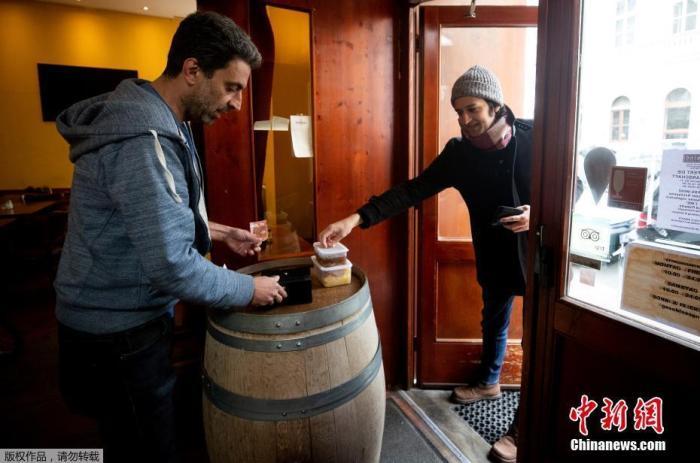 当地时间3月23日,在奥地利维也纳的Steindl餐厅里,服务员鲍勃正在为门口的顾客提供外卖。由于冠状病毒病的传播,奥地利政府宣布餐馆和酒吧关门歇业。Steindl餐厅的员工决定转型做外卖,顾客站在门外取餐。