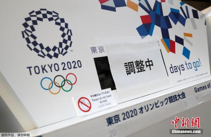 """资料图:3月25日,在日本东京中央区,一间写字楼内的原本显示东京奥运会倒计时的电子屏被贴上了""""正在调整"""",下方奥运会的原定举办日期也被遮挡了起来。"""