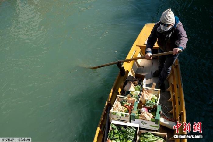 当地时间3月25日,意大利威尼斯,一名男子划船为水城的居民提供日常蔬菜水果。