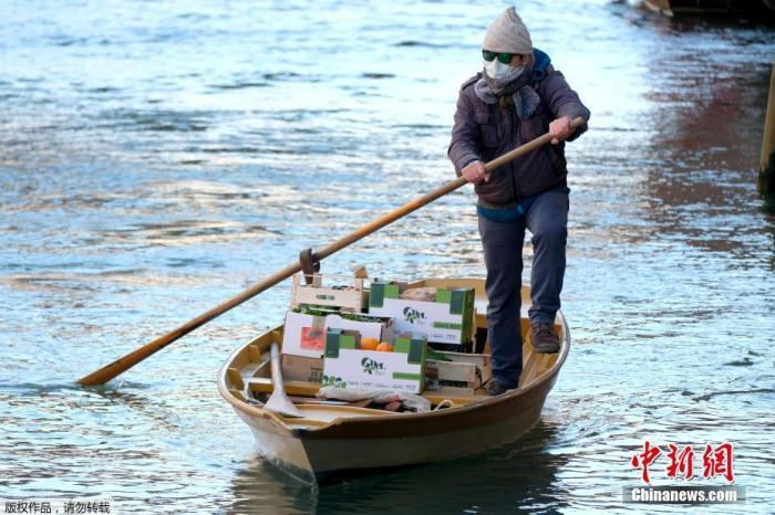 资料图:当地时间3月25日,意大利威尼斯,一名男子划船为水城的居民提供日常蔬菜水果。