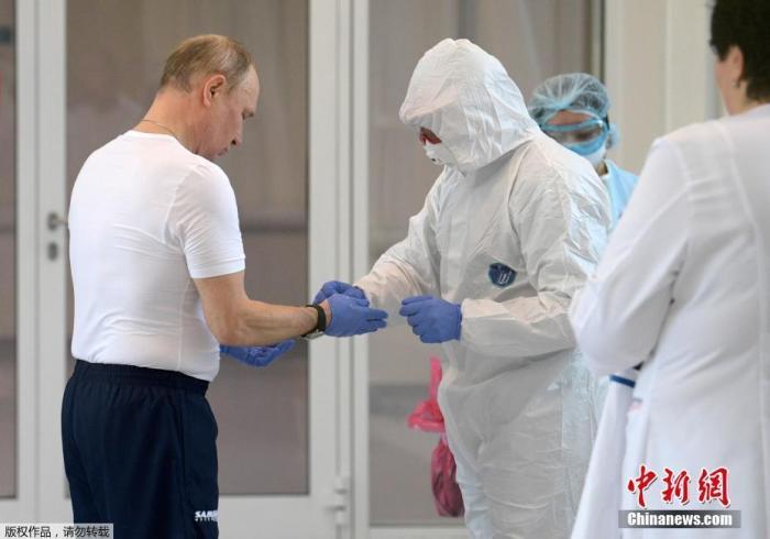 资料图:俄罗斯总统普京在视察医院结束后,脱下防护手套。
