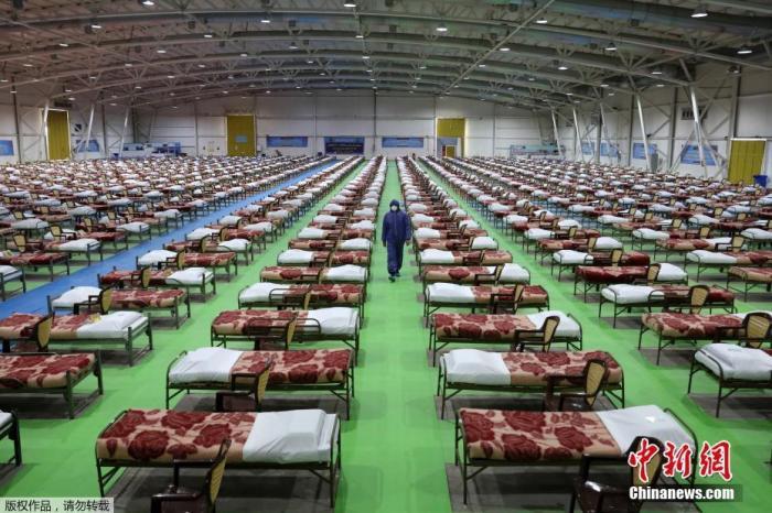 当地时间3月26日,伊朗德黑兰国际展览中心,士兵行走在刚建设好的医疗中心的床位之间。