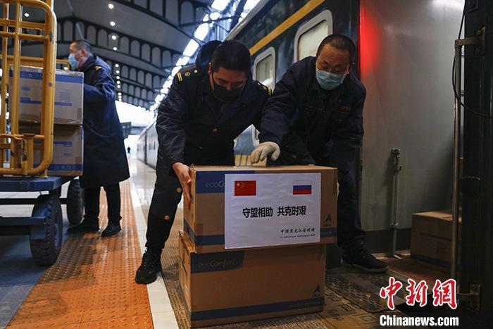 3月28日晚,黑龙江省向俄罗斯克拉斯诺亚尔斯克边区政府捐赠的300套防护服和5万只一次性医用外科口罩由哈尔滨站发出,将经黑河口岸出境,运往俄罗斯克拉斯诺亚尔斯克边区。图为工作人员将捐赠物资搬运上列车。 <a target='_blank' href='http://www.chinanews.com/'>中新社</a>记者 吕品 摄