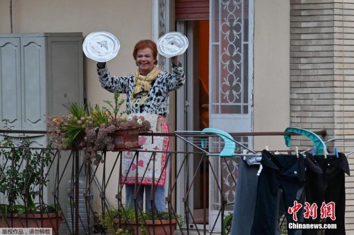 """意大利罗马,一位居民用锅盖敲钹,参加名为""""从窗户往外看,我的罗马""""(Look out from the window, Rome mine !)的音乐快闪活动。"""