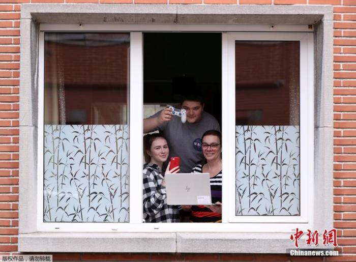 比利時布魯塞爾,當地居民Cathou和她的孩子在窗前展示在居家抗疫的這段期間對自己有意義重大的物品。