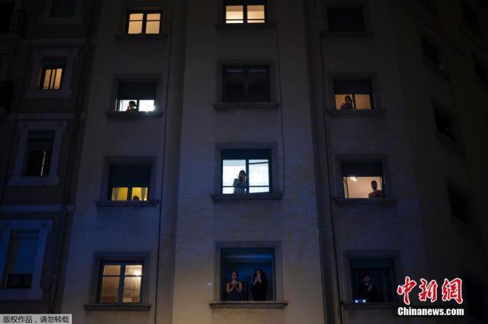 西班牙巴塞罗那,当地民众在窗户前鼓掌致敬战斗在抗击新冠病毒疫情中的医务人员。