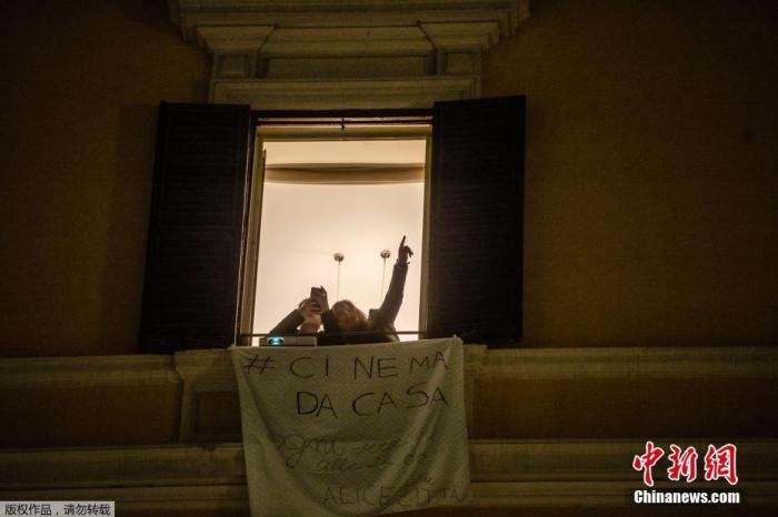 资料图:意大利罗马,Fabia Bettini对儿子指着街对面建筑上投放的电影《西班牙广场的女孩》。这也是罗马电影节的活动之一,旨在鼓励民众在意大利新冠病毒疫情期间留在家中。