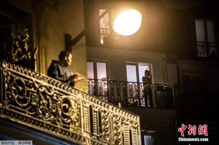 法国巴黎,在阳台上的居民与与法国各地的民众一起鼓掌向医护人员表示支持。