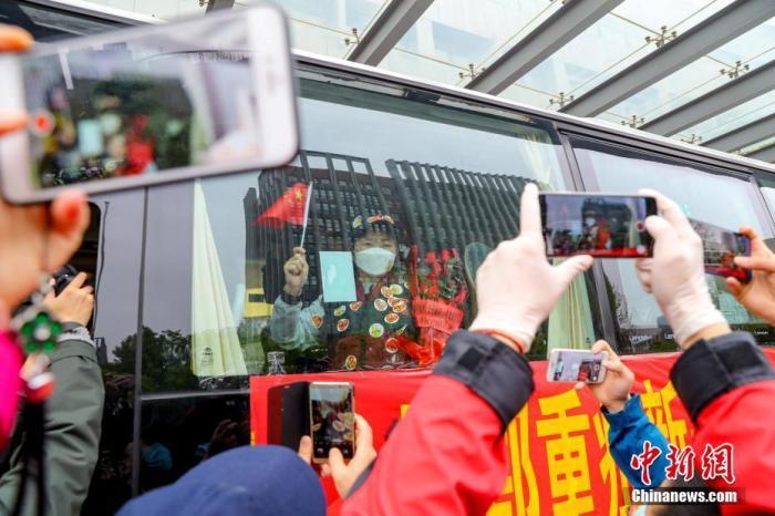 3月31日,由国家卫健委高级别专家组成员、中国著名传染病学专家李兰娟院士带领的国家紧急医疗队启程离开武汉。图为李兰娟院士向送别人群挥手致意。 中新社记者 张畅 摄
