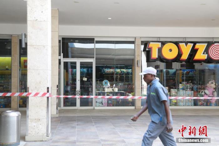 """当地时间4日1日,南非约翰内斯堡,关闭的玩具店前已经拉起警戒线,只有个别建筑工人从外面经过。受疫情影响,南非已经实施全国范围""""封城""""。 记者 王曦 摄"""