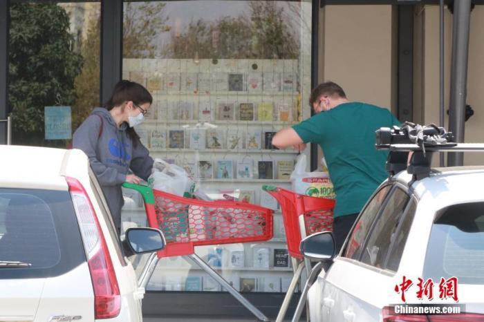 """当地时间4日1日,南非约翰内斯堡,民众戴口罩前往超市购物。受疫情影响,南非已经实施全国范围""""封城""""。 中新社记者 王曦 摄"""